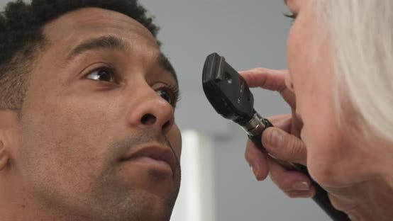 Thumbnail for Tight shot of mature doctor using medical instrument to examine patients eyes