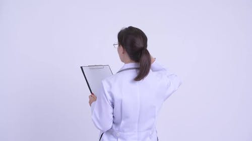 Rear View of Young Woman Doctor Reading on Clipboard While Pointing Finger