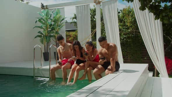 Thumbnail for Multiethnic People Checking Cellphones at Poolside
