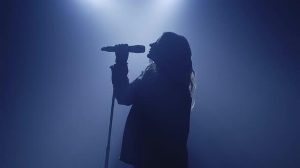 Thumbnail for Hinterleuchtete Silhouette des Sängermädchens, das im dunklen Nachtclub-Discostudio steht und mit dem Singen beginnt