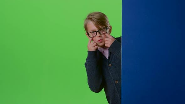 Thumbnail for Teen in Glasses Comes From Behind the Wall and Shows Tongue on a Green Screen
