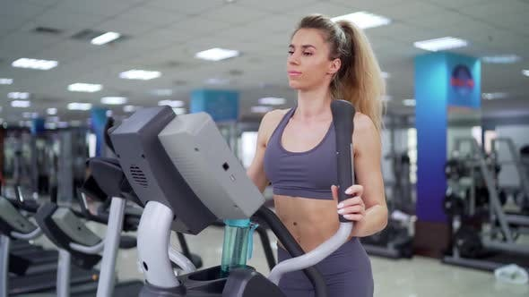 Young woman working out on orbi track at gym exercising