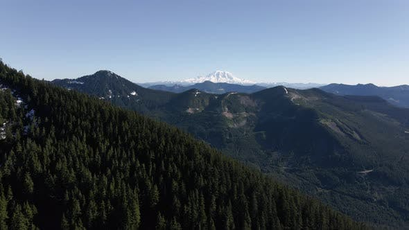 Thumbnail for Parallax Mountain Ridge Aerial With Mt Rainier Behind Forest Trees