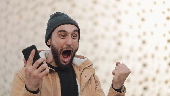 Thumbnail for Euphoric Man Celebrating Sport Victory or Good News Using a Smart Phone in the Street Near Shopping