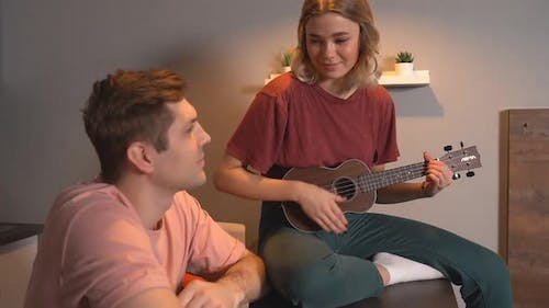 Young Woman Playing Guitar, Ukulele To Her Favorite Guy, Sitting at Home