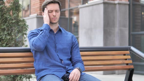 Cover Image for Headache, Tense Young Man Sitting Outdoor on Bench