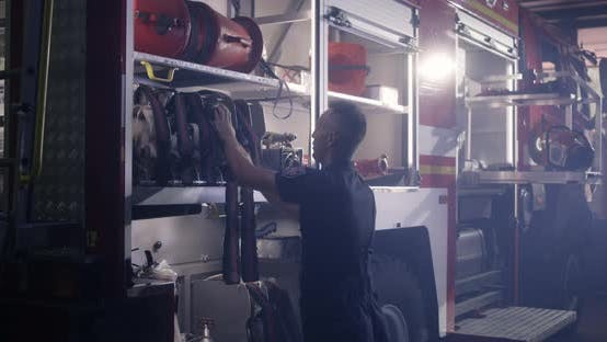Thumbnail for Fireman Putting Hoses Into Fire Engine