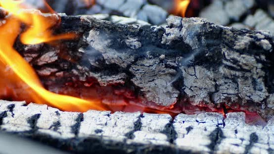 Coals Burn in Bright Flames with Smoke