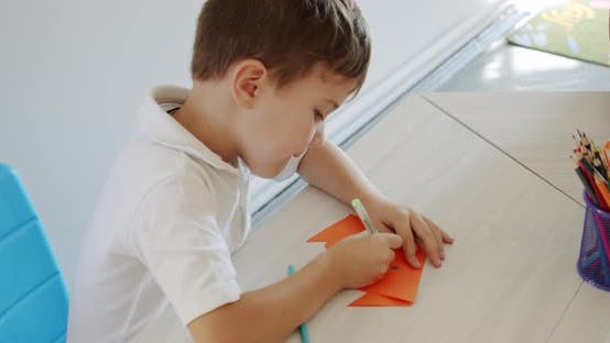 Little Cute Boy Draws with Pencils Is Engaged in Creativity at Home or in Kindergarten, Preparation