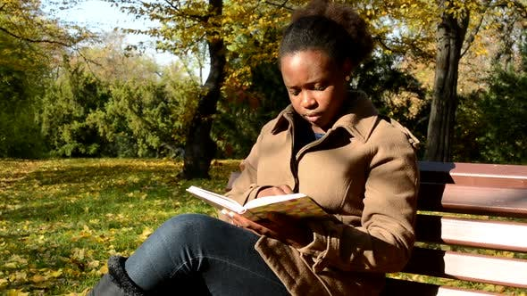 Thumbnail for Young Beautiful African Calm Girl Sits on Bench in Woods, Examines Book and Observes Landscape
