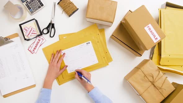 Thumbnail for Woman Signing Parcel Envelopes at Post Office