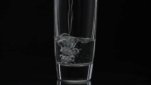 Thumbnail for Pouring Up Shot of Vodka Into Drinking Glass. Slow Motion. Black Background