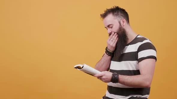 Man with Long Facial Hair Reads a Book and Arranges His Beard