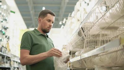 Bearded Man is Choosing Lamp in a Building Material Stores Unpacking It