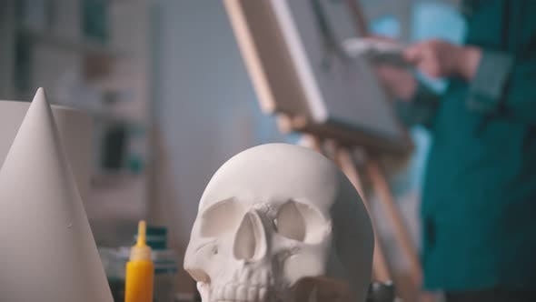 Cover Image for A Young Woman Artist Drawing a Painting in the Art Studio - a Skull and Other Figures on the Table