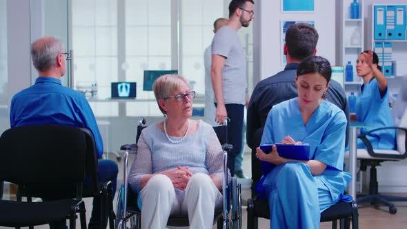 Thumbnail for Nurse Filling Documents While Talking with Disabled Senior Woman