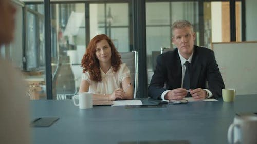 Two business people sitting at the meeting table during a consult with a law firm.