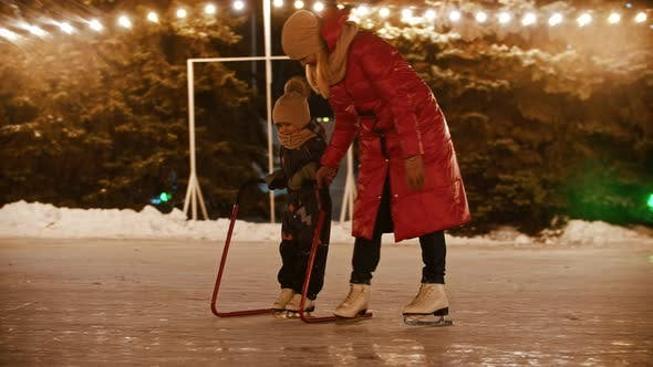 Thumbnail for A Young Woman Skating on the Ice Rink with Her Little Daughter - Skating with Hockey Goal