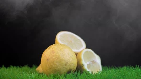 Thumbnail for Halves of lemons on green grass against black background