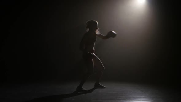 Thumbnail for Champion Boxer Sends the Punches. Silhouette. Lights Rear. Black Background. Side View