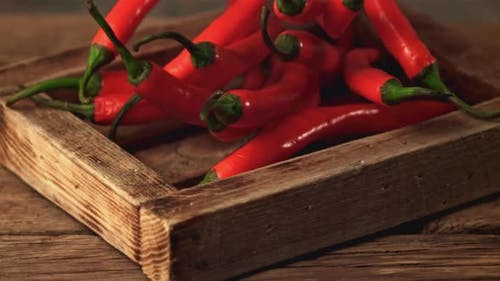 Super Slow Motion Tray with Chilli Pepper Falls on the Table
