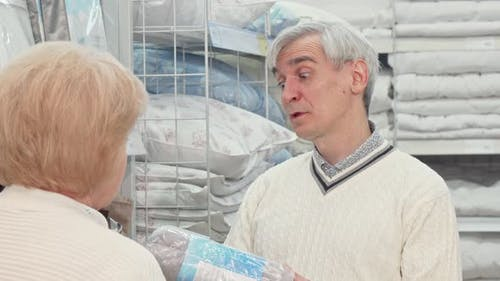 Senior Man Choosing Bedding Goods with His Wife at Furnishings Store