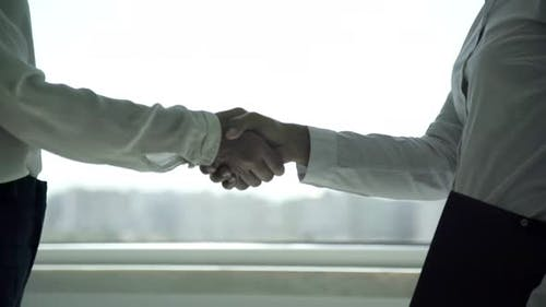 Mid Section of Businesswomen Shaking Hands