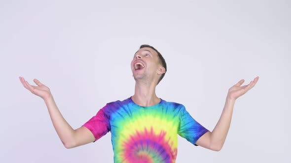 Thumbnail for Studio Shot of Happy Man with Tie-dye Shirt Catching Something