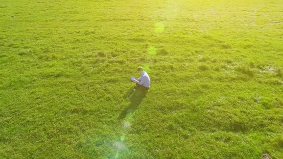 Thumbnail for UHD Aerial View. Low Orbital Flight Over Businessman Sitting on Green Grass with Notebook Pad