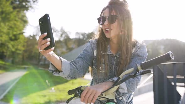 Caucasian Girl in Sunglasses with Bicycle, Making Selfie Photo on Mobile Phone