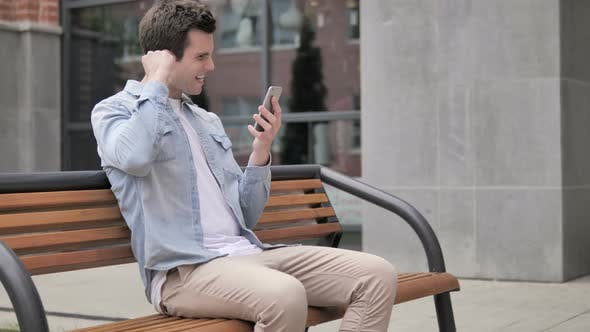 Thumbnail for Outdoor Young Man Excited for Success on Smartphone