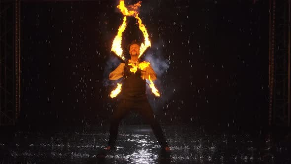 Silhouette of a Man Doing a Professional Fire Show in a Dark Studio in the Rain. Slow Motion