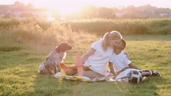 Thumbnail for Mom and Son Are Resting in the Park with Their Dog