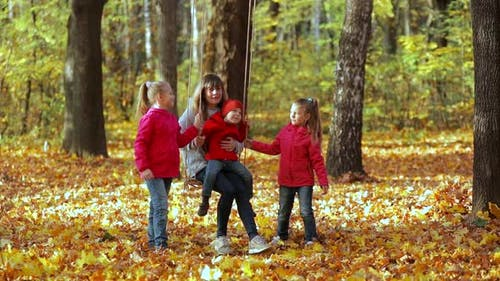 Mom swings children on a rope swing. Happy family in nature in autumn.