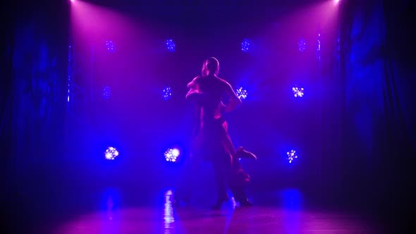 Handsome Man and Woman Dancing Latin Tango Dance Among Beautiful Light. Silhouettes of Dancers on a