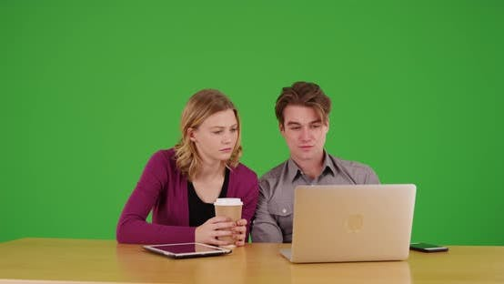 Male and female coworkers watching video on laptop on green screen