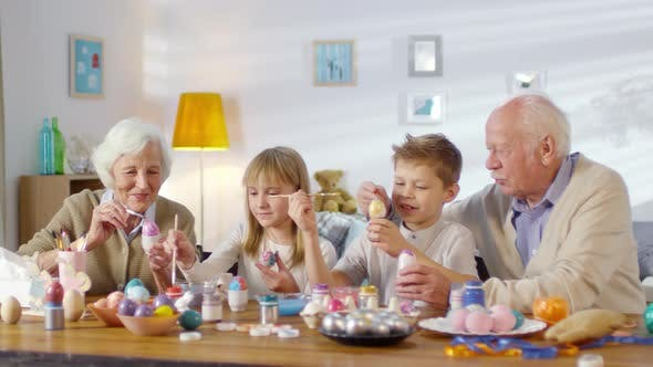 Thumbnail for Grandparents and Grandchildren Painting Eggs and Smiling