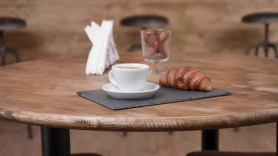 Slide in a Minimalist Composition of a Coffee and a Croissant on a Dark Stone Tray