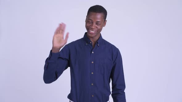 Young Happy African Businessman Waving Hand at Camera