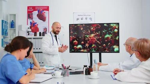 Specialist Medic Explaining Virus Development Pointing on Monitor