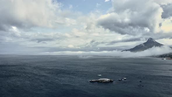 Beautiful Mountain Behind Thick Foggy Skies and Blue Sea Water