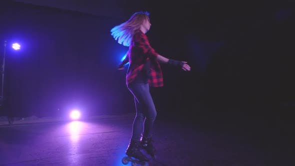 Charming Blonde Girl in Protective Gloves on Rollerblades Starts Professionally Spinning on Front