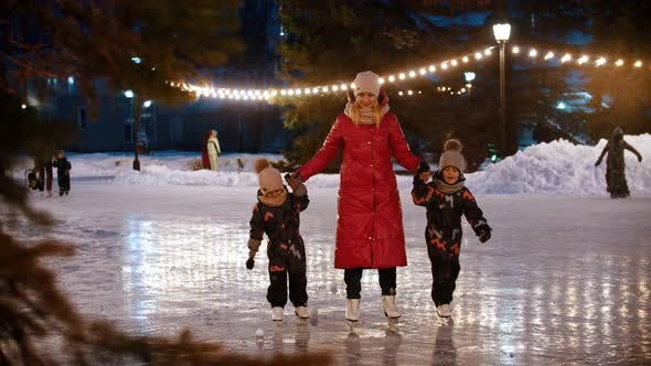 Thumbnail for A Family of Young Mother and Two Kids Skating on the Decorated Ice Rink