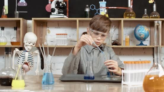 Laboratory Experience in a Chemistry Lesson, Boy in Protective Glasses Pours a Blue Liquid Into a
