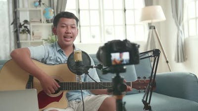 Asian Boy Is A Vlogger. Boy With Guitar Talking To Camera. The Boy Is Streaming