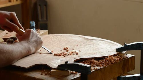 Luthier Carving a Guitar
