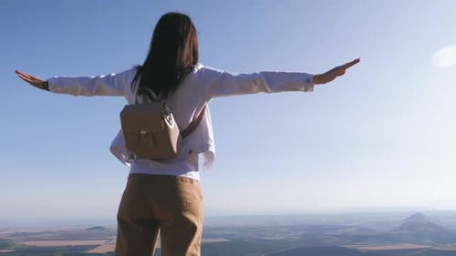 Successful Girl Hiker Open Arms in the Sky After Hiking To Mountain Top Summit Above the Clouds.