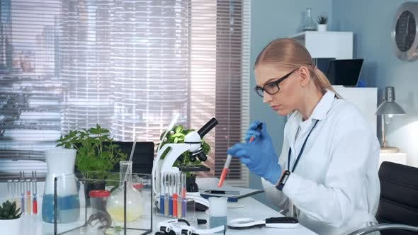 In Modern Research Laboratory Female Scientist Using Pipette to Drop Sample on Slide