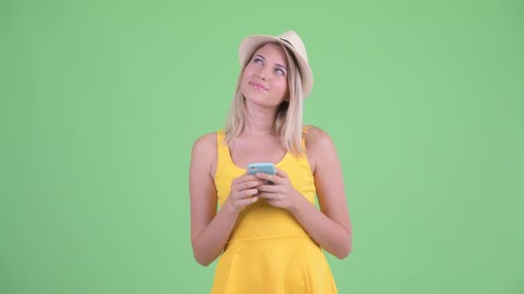 Thumbnail for Happy Young Blonde Tourist Woman Thinking While Using Phone