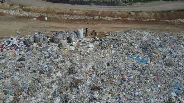 Thumbnail for Aerial View of City Garbage Dump. Family with Children Separates Trash To Gain Some Money